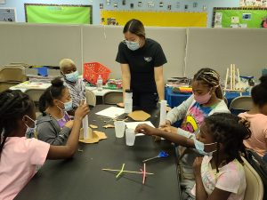 Four girls at The Well Experience with two instructors work on building their Summer STEM rockets
